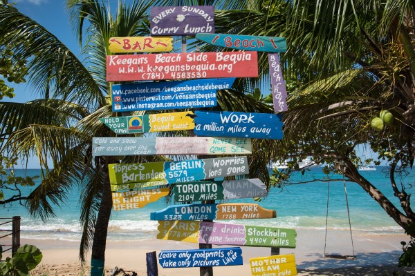 Humorous directional beach signs along side a beautiful sandy beach in Bequia Caribbean.